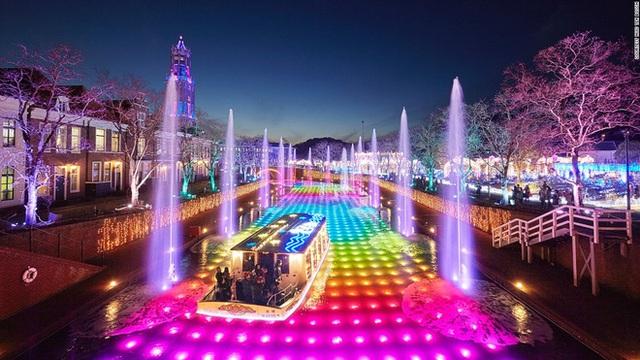 Chiếc thuyền gắn đầy đèn neon bơi trên mặt nước cũng toàn màu sắc rực rỡ…