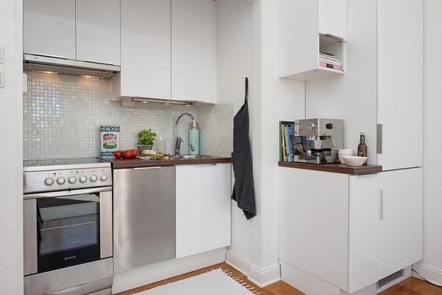 Để khắc phục diện tích nhỏ của bếp, chủ nhân của căn hộ không tiếc tiền đầu tư những thiết bị hiện đại. Lò nướng, tủ lạnh và thậm chí máy giặt đều được tích hợp thành một tổng thể gắn kết gọn gàng. Hệ thống tủ bếp cao sát trần giúp tăng thêm diện tích cất trữ đồ đạc.