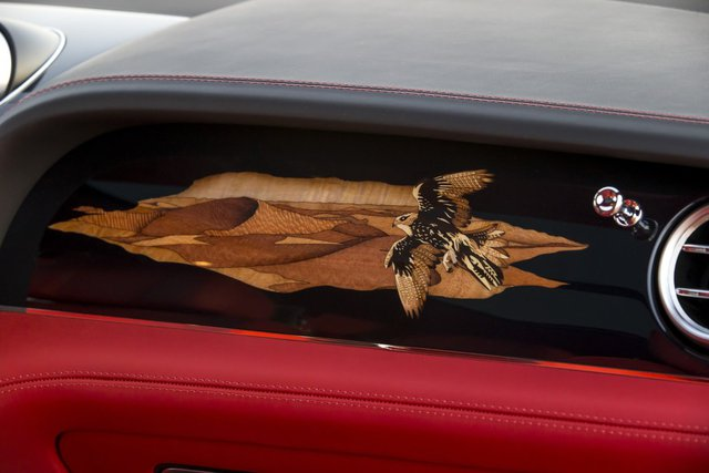Phía trước ghế phụ được trang trí bằng hình vẽ chim ưng đang bay trên Sa Mạc trên nền đen của gỗ ốp.