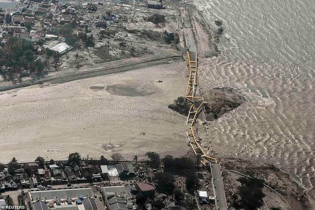 Thảm cảnh máy xúc đào mồ chôn tập thể cho các nạn nhân động đất, sóng thần Indonesia - Ảnh 11.