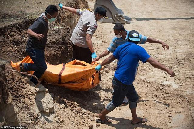 Thảm cảnh máy xúc đào mồ chôn tập thể cho các nạn nhân động đất, sóng thần Indonesia - Ảnh 2.