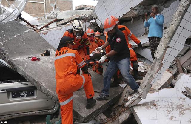Thảm cảnh máy xúc đào mồ chôn tập thể cho các nạn nhân động đất, sóng thần Indonesia - Ảnh 6.
