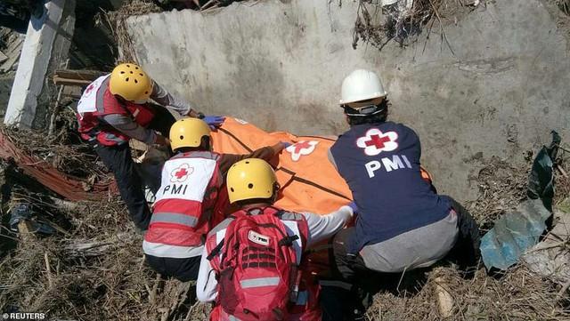 Thảm cảnh máy xúc đào mồ chôn tập thể cho các nạn nhân động đất, sóng thần Indonesia - Ảnh 7.