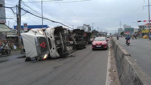 Xe đầu kéo lật ngang trên QL1A,hàng trăm thùng bia đổ tràn ra đường - Ảnh 1.