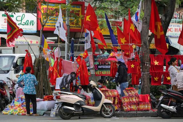 Người TP HCM nườm nượp mua sẵn cờ, áo đỏ cổ vũ tuyển Việt Nam - Ảnh 1.