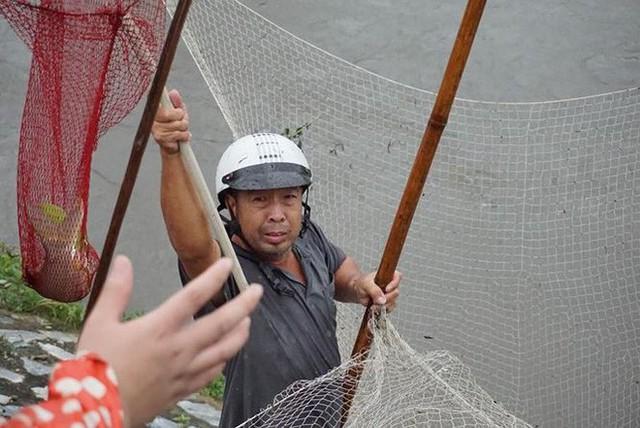 Người Hà Nội đổ xô ra sông bắt cá sau cơn mưa - Ảnh 9.