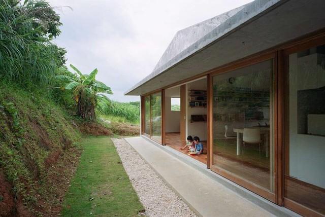 Mặt sau nhà thiết kế dựa vào lưng đồi, mái hiên rộng làm sân chơi cho những đứa trẻ.