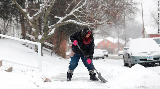 Người dân dọn tuyết bên ngoài ngôi nhà của mình. Các nhà khí tượng học cảnh báo những gì tồi tệ nhất vẫn chưa xảy ra.