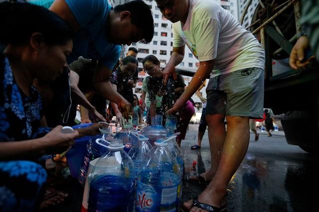 Dân Hà Nội xuyên đêm xếp hàng lấy nước sạch sau vụ nước sông Đà nhiễm dầu - Ảnh 14.