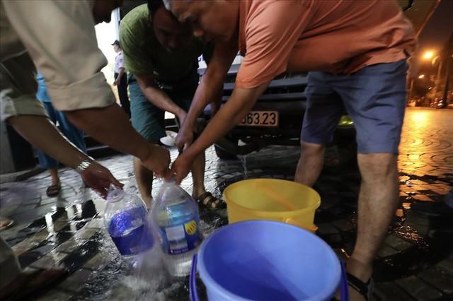 Dân Hà Nội xuyên đêm xếp hàng lấy nước sạch sau vụ nước sông Đà nhiễm dầu - Ảnh 4.
