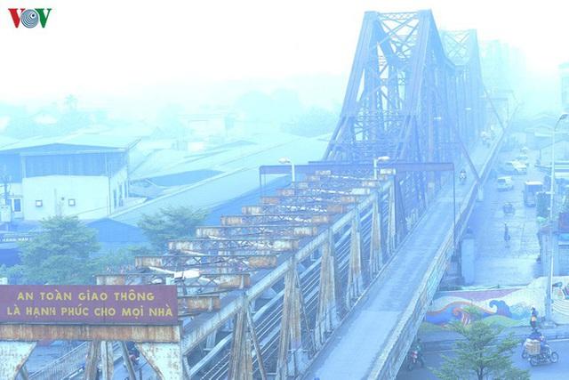 Phố phường Hà Nội chìm trong mịt mù sương, bụi dù vào giữa trưa - Ảnh 2.