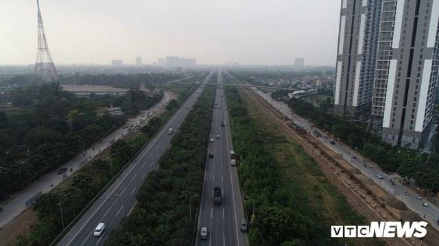 Ảnh: Công nhân xén dải phân cách, mở rộng đường gom Đại lộ Thăng Long - Ảnh 1.