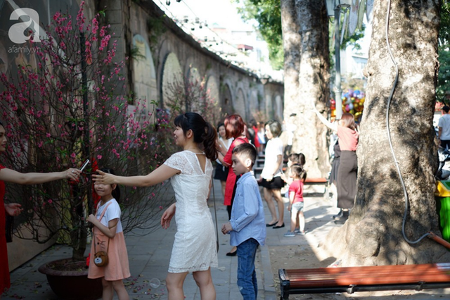 Nắng đẹp, người Hà Nội rủ nhau xuống phố du xuân, xúng xính áo dài chụp ảnh đầu năm mới - Ảnh 11.
