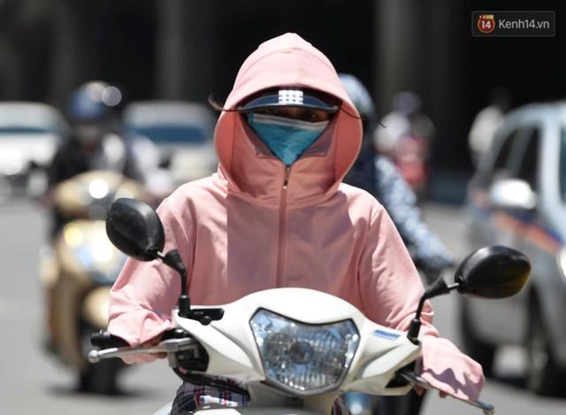 Ảnh: Người dân Thủ đô vật vã chống chọi với nắng nóng kinh hoàng trên 40 độ C, khăn mặt ướt trùm đầu trở thành vật cứu cánh - Ảnh 1.