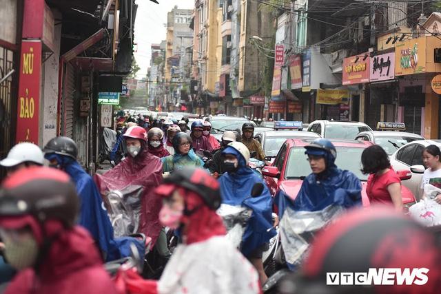 Ảnh: Xe cộ ùn tắc khắp ngả, người dân vất vả mưu sinh dưới trời mưa bão ở Thủ đô - Ảnh 4.