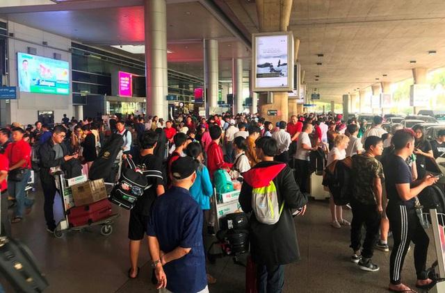 Ngủ gục ở sân bay Tân Sơn Nhất đón Việt kiều về quê ăn tết - Ảnh 1.