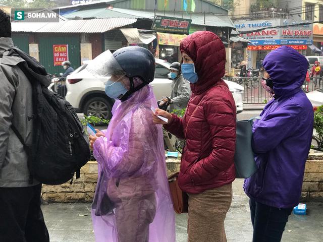 Người dân bỏ làm, đội mưa lạnh đứng đợi nhận khẩu trang miễn phí tại chợ thuốc lớn nhất Hà Nội - Ảnh 1.