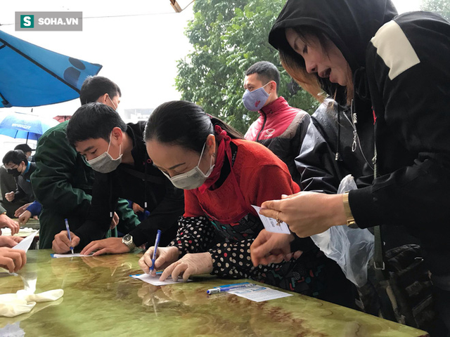 Người dân bỏ làm, đội mưa lạnh đứng đợi nhận khẩu trang miễn phí tại chợ thuốc lớn nhất Hà Nội - Ảnh 5.