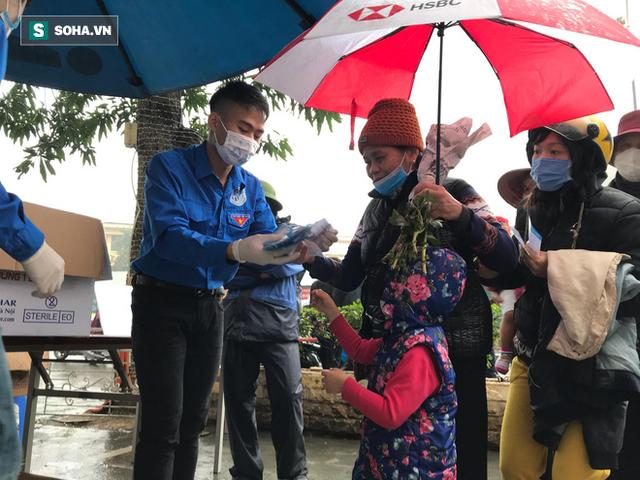 Người dân bỏ làm, đội mưa lạnh đứng đợi nhận khẩu trang miễn phí tại chợ thuốc lớn nhất Hà Nội - Ảnh 8.