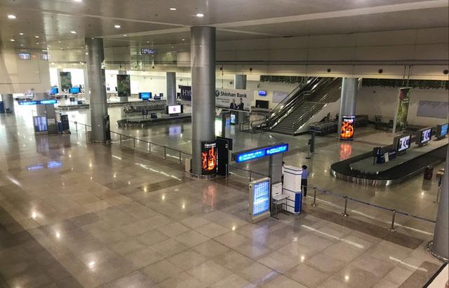 Người dân mặc đồ bảo hộ kín mít ra sân bay, ga quốc tế Tân Sơn Nhất hoang vắng lạ thường - Ảnh 1.
