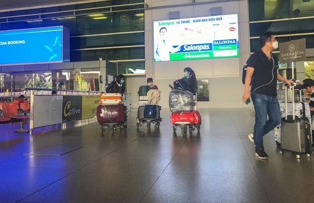 Người dân mặc đồ bảo hộ kín mít ra sân bay, ga quốc tế Tân Sơn Nhất hoang vắng lạ thường - Ảnh 11.