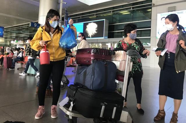 Người dân mặc đồ bảo hộ kín mít ra sân bay, ga quốc tế Tân Sơn Nhất hoang vắng lạ thường - Ảnh 12.
