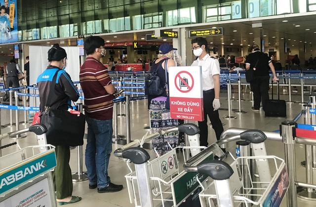 Người dân mặc đồ bảo hộ kín mít ra sân bay, ga quốc tế Tân Sơn Nhất hoang vắng lạ thường - Ảnh 6.
