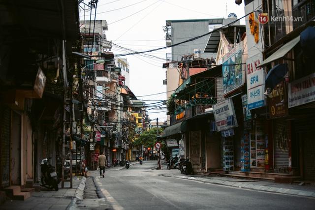 Chùm ảnh: Hà Nội đón mưa dày hạt do không khí lạnh, đường phố càng thêm vắng vẻ giữa những ngày cách ly xã hội - Ảnh 1.