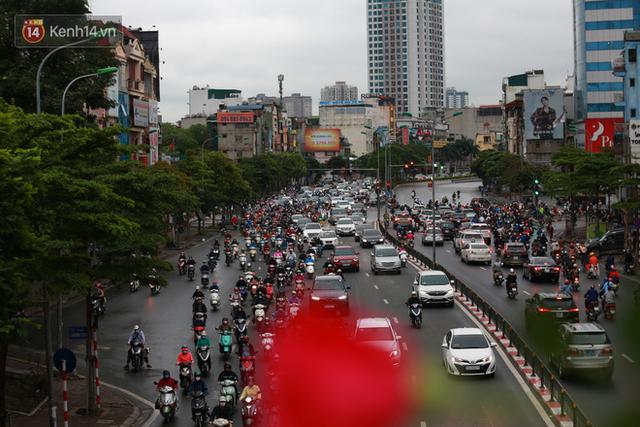 Ảnh: Ngày đầu tiên sau khi nới lỏng cách ly xã hội, đường phố Hà Nội đông đúc kéo dài, người dân chật vật đi làm dưới mưa - Ảnh 5.