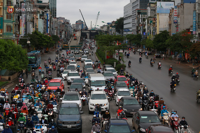 Ảnh: Ngày đầu tiên sau khi nới lỏng cách ly xã hội, đường phố Hà Nội đông đúc kéo dài, người dân chật vật đi làm dưới mưa - Ảnh 6.