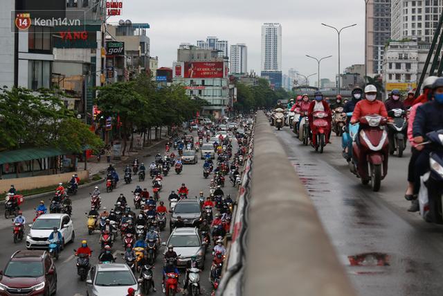 Ảnh: Ngày đầu tiên sau khi nới lỏng cách ly xã hội, đường phố Hà Nội đông đúc kéo dài, người dân chật vật đi làm dưới mưa - Ảnh 7.