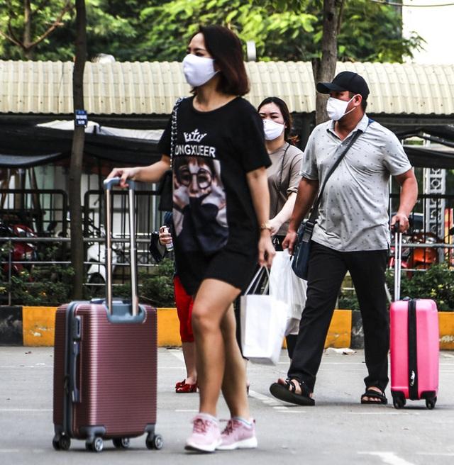 Người dân tay xách nách mang đồ đạc về quê nghỉ lễ 30/4, xe khách được phun khử khuẩn trước khi xuất bến - Ảnh 1.