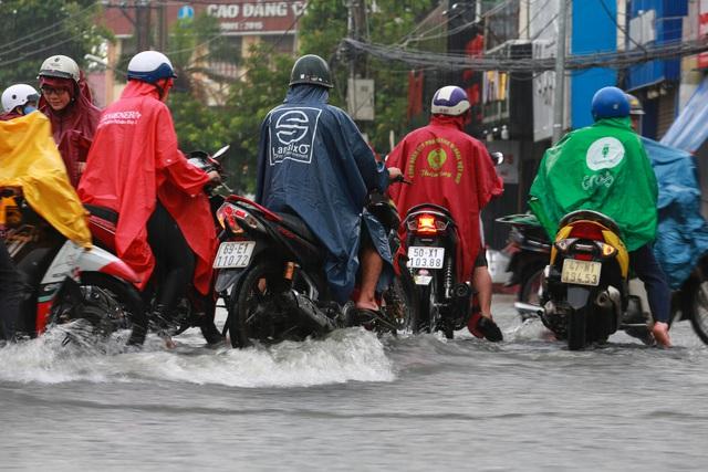 [ẢNH] Nước chảy xiết kéo nhiều xe máy đổ nhào giữa phố Sài Gòn, người dân dắt bộ cho an toàn - Ảnh 2.