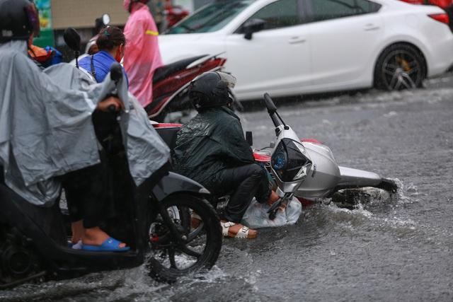 [ẢNH] Nước chảy xiết kéo nhiều xe máy đổ nhào giữa phố Sài Gòn, người dân dắt bộ cho an toàn - Ảnh 3.