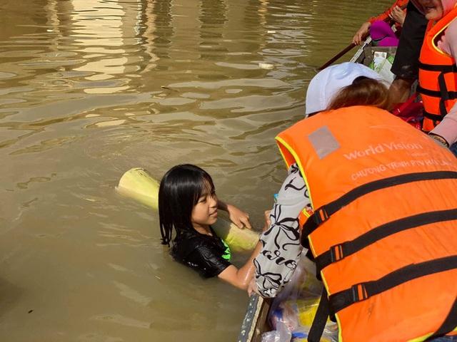 Bơi xuồng trong lũ nhận quà cứu trợ  - Ảnh 2.