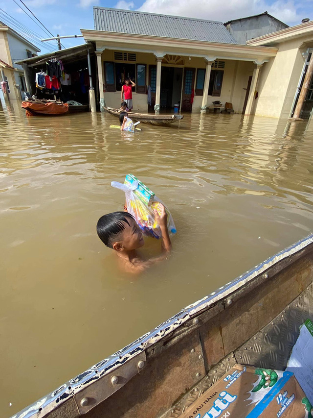 Bơi xuồng trong lũ nhận quà cứu trợ  - Ảnh 4.