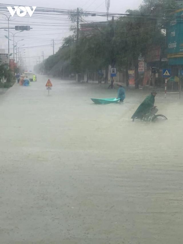 Công an Hà Tĩnh dầm mình trong mưa lũ cõng dân đi sơ tán - Ảnh 1.