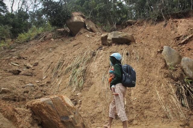 Người dân nín thở đi dưới khối đá 30 tấn lộ ra sau mưa lũ - Ảnh 1.