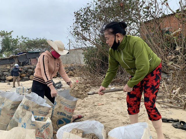 Người dân Quảng Ngãi hối hả ra biển lấy cát chống bão số 9 - Ảnh 1.