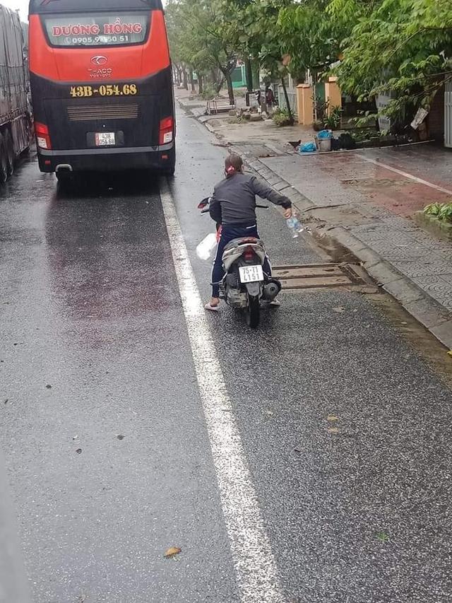 Ấm lòng cảnh người dân Huế dù đang cùng chịu ảnh hưởng bão số 9 vẫn gõ cửa từng chiếc xe xếp hàng trú bão để phát cơm ăn, nước uống miễn phí - Ảnh 2.