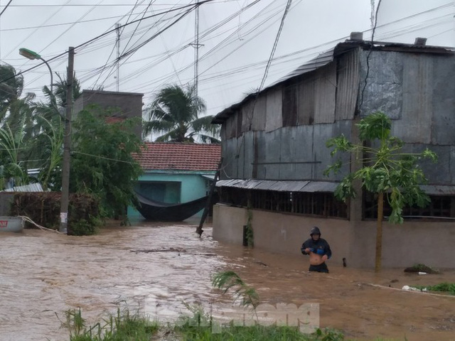 Bão tan nhưng dân phố biển Nha Trang vẫn bì bõm nơi nước ngập - Ảnh 1.