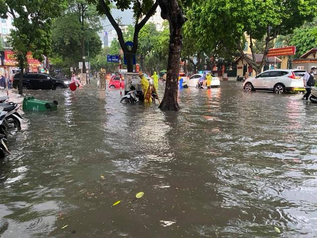 Hà Nội: Mưa to như trút nước lúc tan tầm, nhiều tuyến phố trung tâm lại biến thành sông - Ảnh 1.
