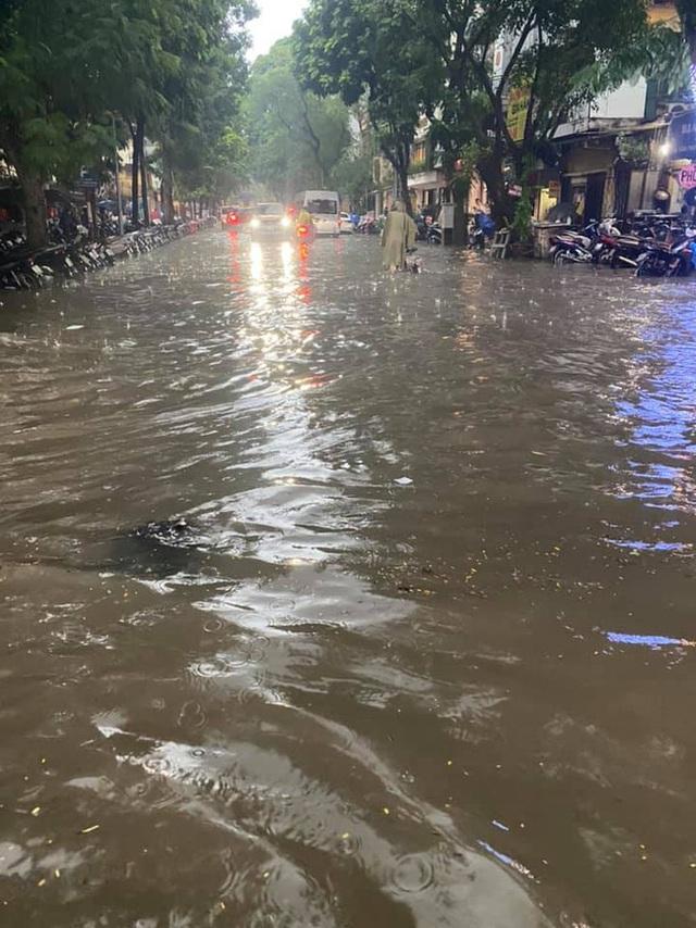 Hà Nội: Mưa to như trút nước lúc tan tầm, nhiều tuyến phố trung tâm lại biến thành sông - Ảnh 4.