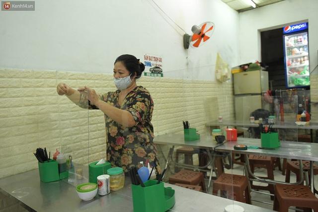Hà Nội trong ngày đầu tiên giãn cách hàng quán: Bàn được lắp vách ngăn, khách ngồi cách xa nhau hơn 1 mét - Ảnh 10.
