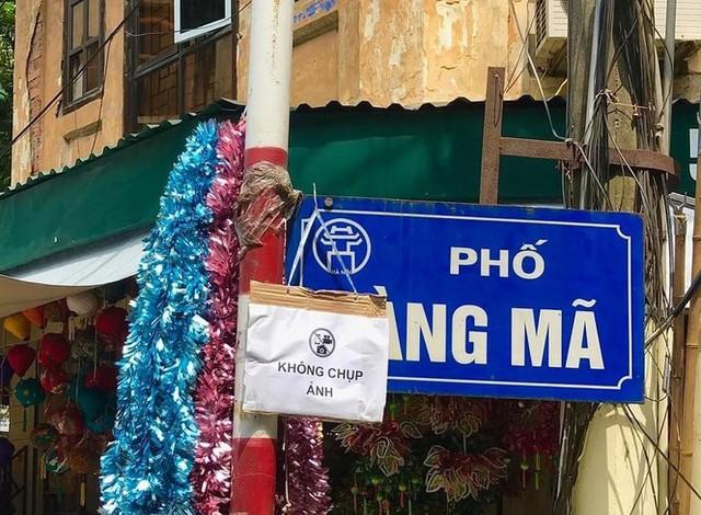 Nhiều chủ quán trên phố Hàng Mã bị xử lý vì treo biển thu tiền chụp ảnh - Ảnh 1.