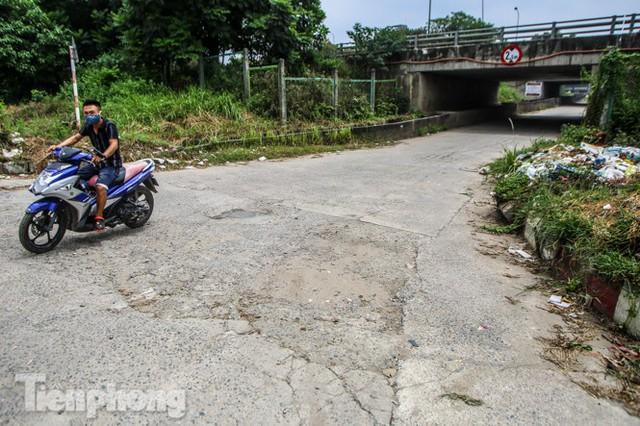 Hầm chui nhếch nhác, chằng chịt ổ gà trên đường gom Đại lộ Thăng Long  - Ảnh 1.