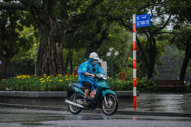 Người dân Thủ đô đón cái lạnh đầu mùa kèm mưa - Ảnh 7.