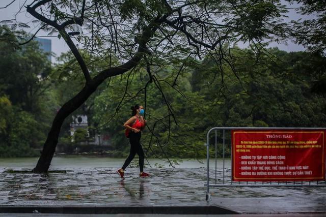 Người dân Thủ đô đón cái lạnh đầu mùa kèm mưa - Ảnh 8.