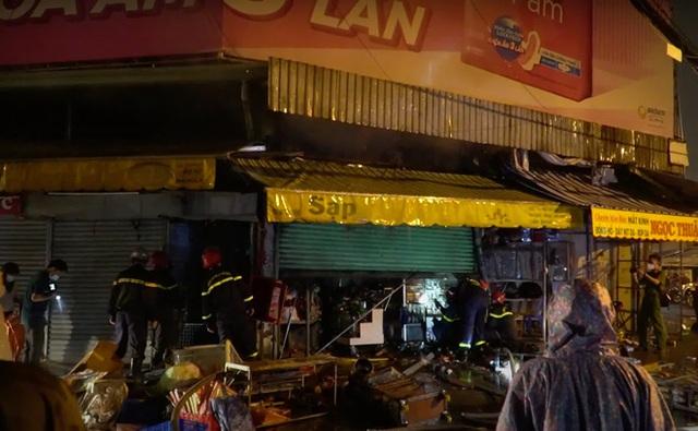 Cảnh sát dầm mưa cắt cửa sắt để dặp tắt đám cháy trong chợ Nhị Thiên Đường - Ảnh 1.