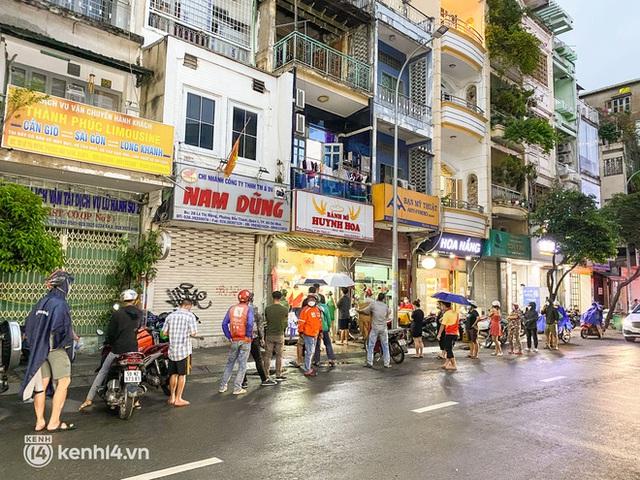 Hàng chục người xếp hàng dưới mưa mua ổ bánh mì đắt nhất Sài Gòn, có khách hốt chục cái ăn trả thù mùa dịch! - Ảnh 1.